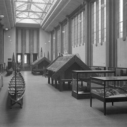 Maori artifacts, particularly waka (canoes) and pataka (storehouses), inside the Maori Hall at the Dominion Museum, Buckle Street, Wellington, circa 1936.