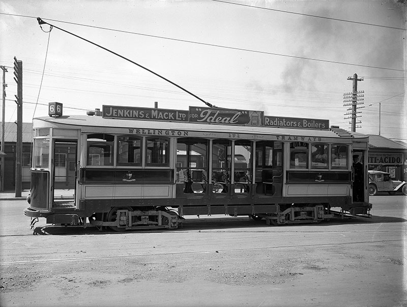 Side view of a Wellington tram. A tram conductor is inside on the right, c. 1920s.