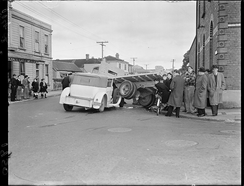 A crowd gathers to look at a collision. The accident took place in front of the Mount Cook Barracks and the Salvation Army at the intersection of Tasman and Buckle Streets in Wellington, 1950.